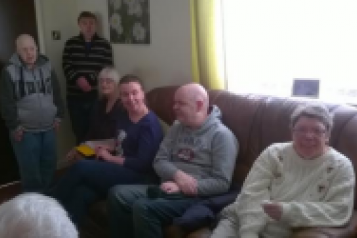 People sat on sofa in care home
