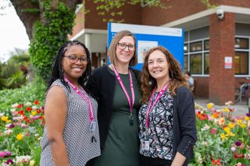 Three Healthwatch staff members standing outside a hospital